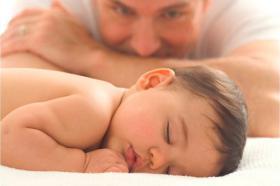 Bebé durmiendo observado por su padre.
